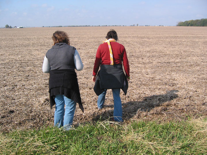 two people walking through a field
