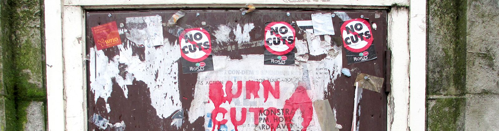 Stencil and stickers on a wall in London with the words No Cuts