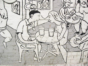 Mural in Oslo, Norway of two cartoon characters sitting at a busy cafe